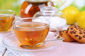 Teapot and cups of tea on table on bright background