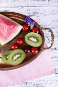 Slices of melon, kiwi and watermelon on metal tray on wooden background