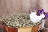 Big round basket with dried grass on sacking background
