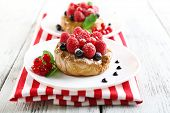 Sweet cakes with berries on table close-up