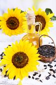 Sunflowers with seeds and oil on table close-up