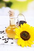 Sunflower with seeds and oil on table on bright background