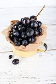 Purple grape in cup on wooden background
