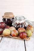 Plum jam and fresh plums in glass dish on piece of paper on wooden table on light background