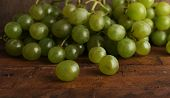 Green grape on wooden table on wooden background