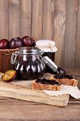 Tasty plum jam in jars and plums on wooden table on wooden background