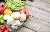 Fresh organic vegetables and fruits on wooden background