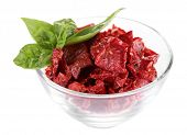 Sun dried tomatoes in glass bowl and basil leaves, isolated on white