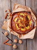 Delicious cake with nuts and cinnamon on wooden table close up