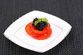 Slices of tomato with black caviar on plate on dark fabric background