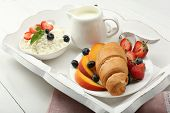 Delicious breakfast with croissant, cottage cheese and fruits