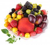 Different berries and fruits in plate isolated on white