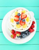 Cottage cheese with fruits and berries in bowl on wooden table