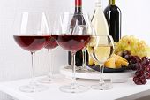 Bottles and glasses of wine, cheese and ripe grapes on table in room