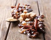 Brown sugar cubes, reed and crystal sugar, spices on wooden background