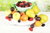 Ripe fruits and berries on table on bright background