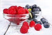 Glass bowls of raspberries and blueberries on wooden table on light background