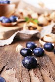 Wooden bowl of blueberries on cutting board on sacking napkin closeup