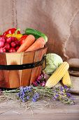 Big round wooden basket with vegetables on sacking background
