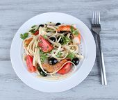 Fresh prawns with spaghetti, olives, tomatoes and parsley in a big round plate on wooden background