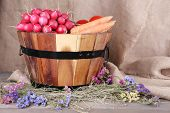Big round basket with dried grass, vegetables, on sacking background