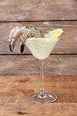 Martini glass of fresh tasty prawns with lemon and sauce on wooden background