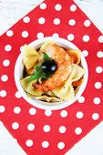 Fresh prawns with coloured macaroni and olives in a round bowl on a napkin on wooden background