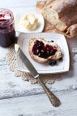 Fresh bread with homemade butter and blackcurrant jam on plate, on light wooden background