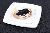 Slice of bread with butter and black caviar on square plate on dark fabric background