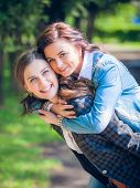 Young and attractive girlfriends have fun in park