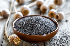 stock photo of opiate  - Poppy seeds with heads on a wooden table  - JPG