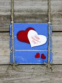 Happy Valentine's Day sign with red hearts hanging on wood fence