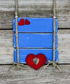 Blank antique blue sign with red hearts hanging on wooden fence