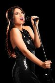 Vertical shot of a beautiful female singer singing into a microphone on black background