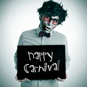 a man dressing a zombie costume with a black signboard with the text happy carnival written in it