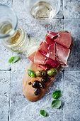 Dry cured ham, marinated olives and white wine (seen from above)