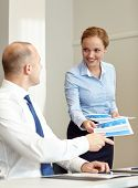 business, people and teamwork concept - smiling woman giving papers to man in office