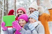 technology, season, friendship and people concept - group of smiling men and women taking selfie tablet pc computer in winter forest