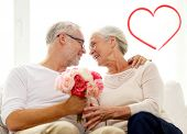 family, holidays, age and people concept - happy senior couple holding bunch of flowers at home with red heart shape