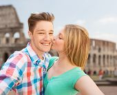 travel, tourism, technology, love and people concept - smiling couple kissing and taking selfie over coliseum background