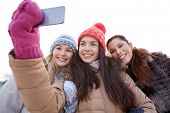 people, friendship, technology, winter and leisure concept - happy teenage girls taking selfie with smartphone outdoors