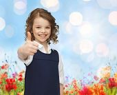 people, gesture, children, summer vacation and happiness concept happy little school girl showing thumbs up over poppy field and blue lights background
