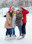 people, friendship, technology and leisure concept - happy friends taking selfie with smartphone on ice skating rink outdoors