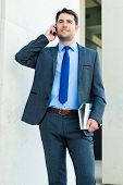 Handsome and confident businessman or manager talking on his business cell phone walking in front of modern architecture
