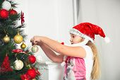 little girl in  red cap hangs on the Christmas tree new year toys