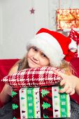 Little girl in gray dress is holding a Christmas gift