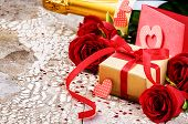 Valentine's Setting With Present And Bouquet Of Red Roses