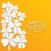 Glossy folded paper shamrock leaves on yellow background for Happy St. Patrick's Day celebration.