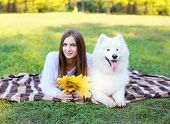 Portrait Happy Pretty Woman And White Samoyed Dog Resting On The Plaid Outdoors In Warm Sunny Day