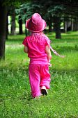 Little fashionable girl all in pink walking in the grove
